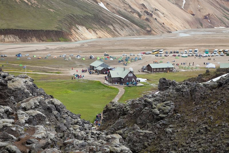 Hut and campground beneath rhyolite mountains at Landmannalaugar, Sudhurland, Iceland.