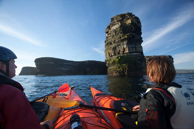 Sea kayakers admiring Dun Briste seastack, Downpatrick Head, Co Mayo, Ireland.