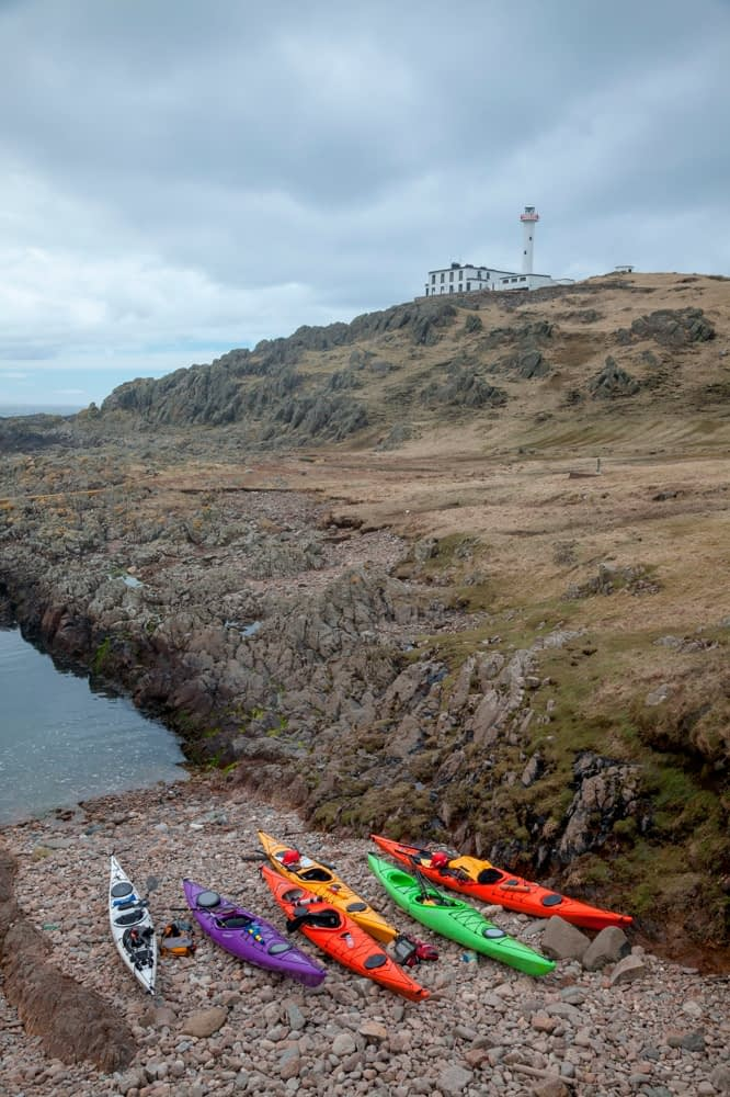 Sea kayaks beneath the lighthouse on Inishtrahull, Ireland's most northerly island. County Donegal, Ireland.