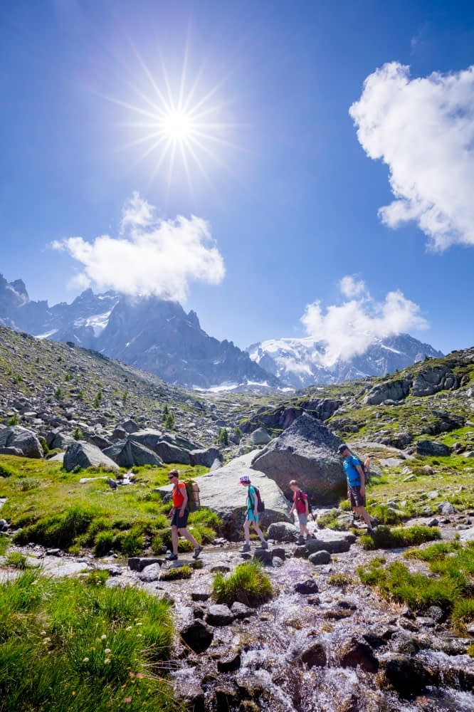 Hikers crossing a stream on the Grand Balcon Nord, Chamonix Valley, French Alps, France.