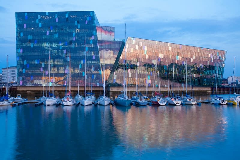Harpa Concert Hall and waterfront yachts at dusk, Reykjavik, Iceland.