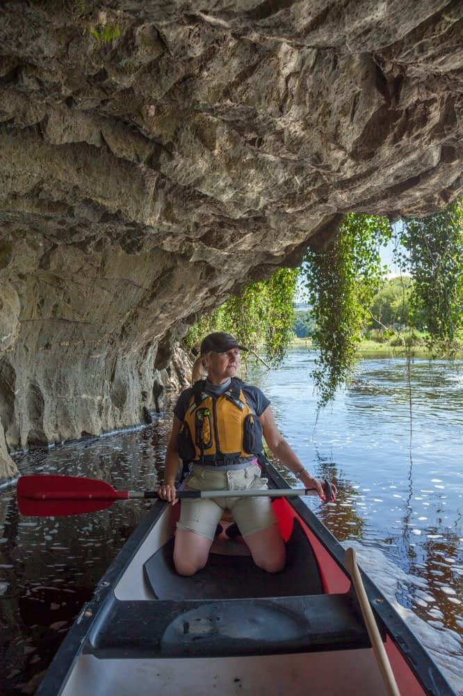 Canoeist beneath a limestone cliff, Blackwater River, Mallow, County Cork, Ireland.