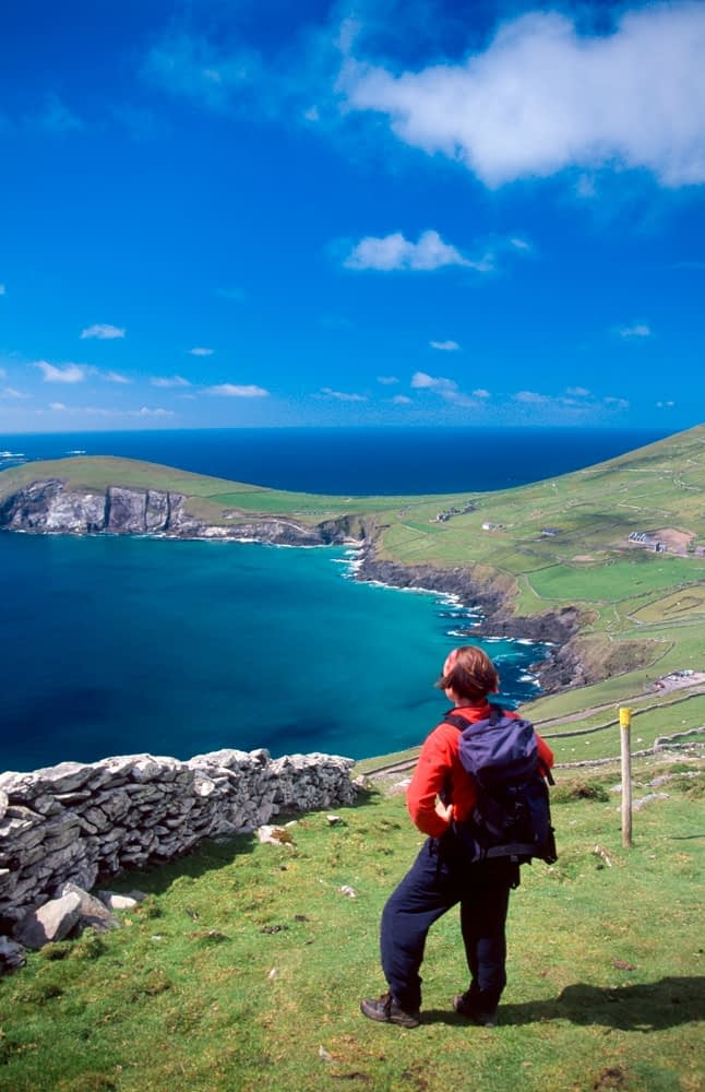 Walker looking over Coumeenoole Bay from the Dingle Way, Co Kerry, Ireland.