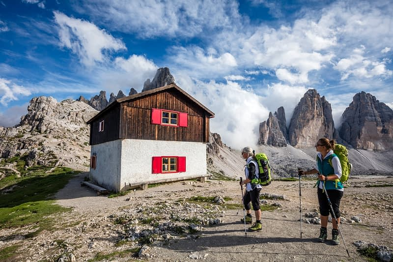 Hikers and hut beside Rifugio Locatelli, Tre Cime di Lavaredo, Sexten Dolomites, South Tyrol, Italy.