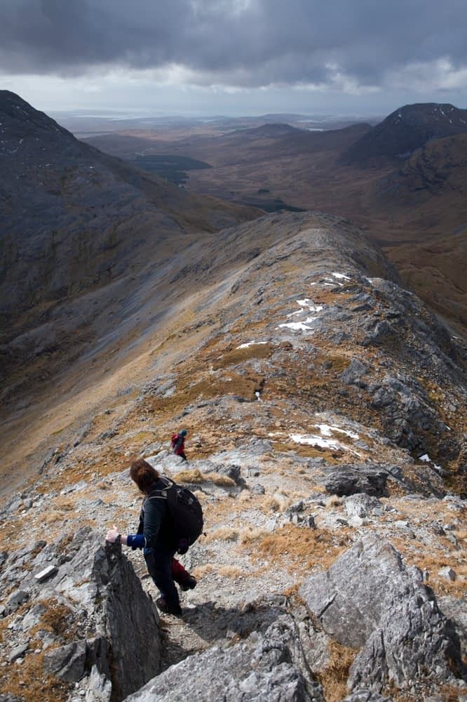 Descending the narrow ridge from Bencollaghduff to Maumina, Twelve Bens, Connemara, Co Galway, Ireland.