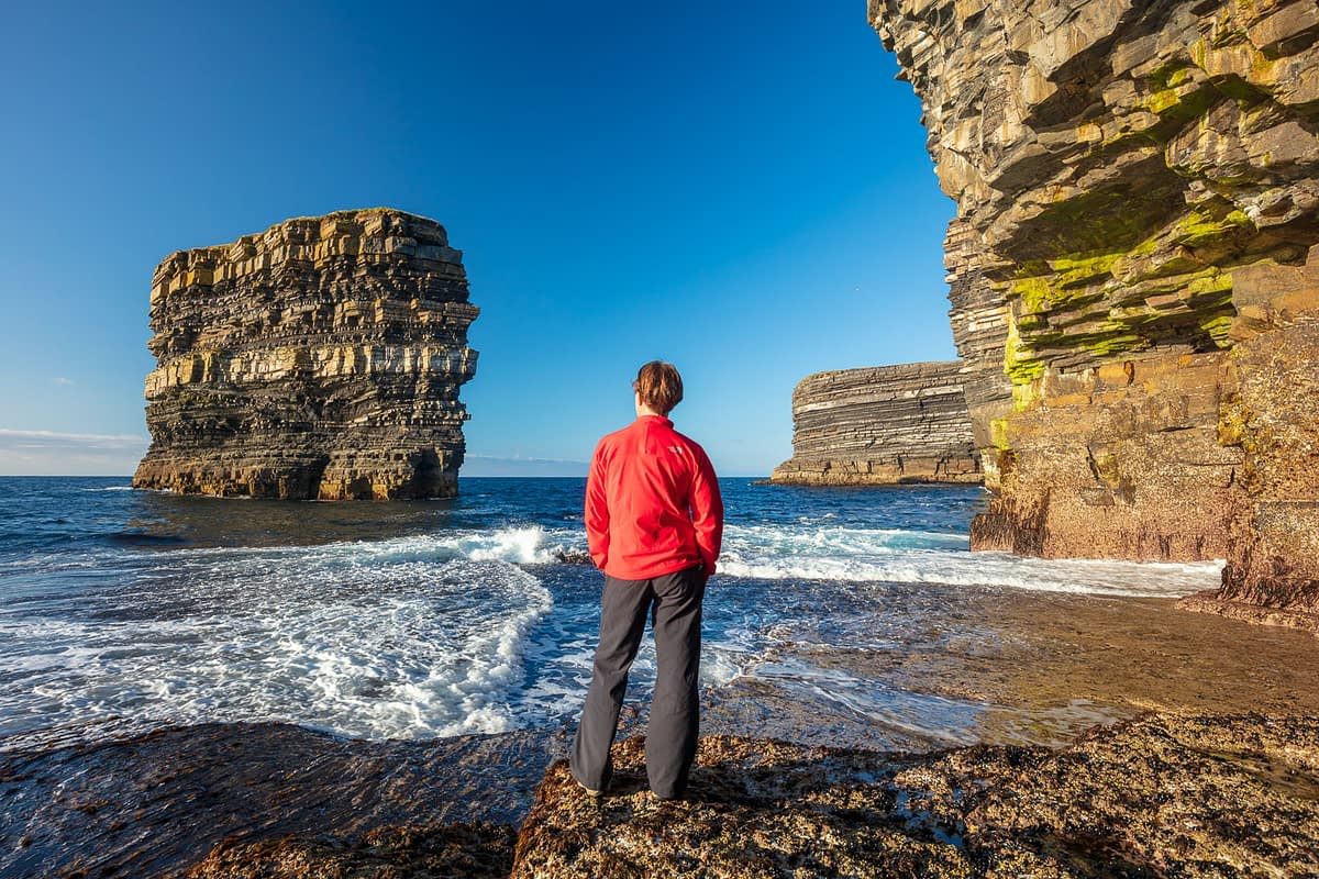 Person admiring Dun Briste sea stack from the shore beneath Downpatrick Head. County Mayo, Ireland.