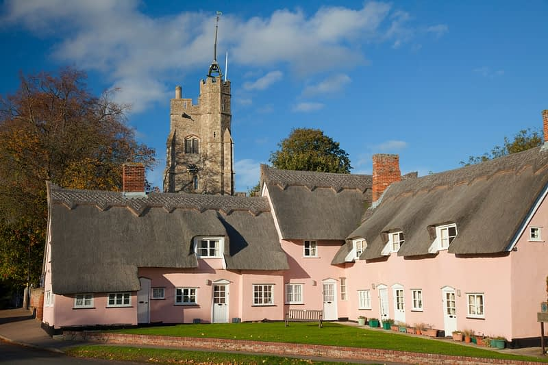 The Pink Cottages beneath St Mary's church, Cavendish, Suffolk, England.