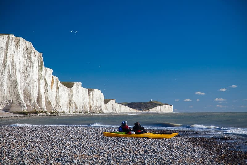 Kayakers at the Seven Sisters, Cuckmere Haven beach, County Sussex, England.