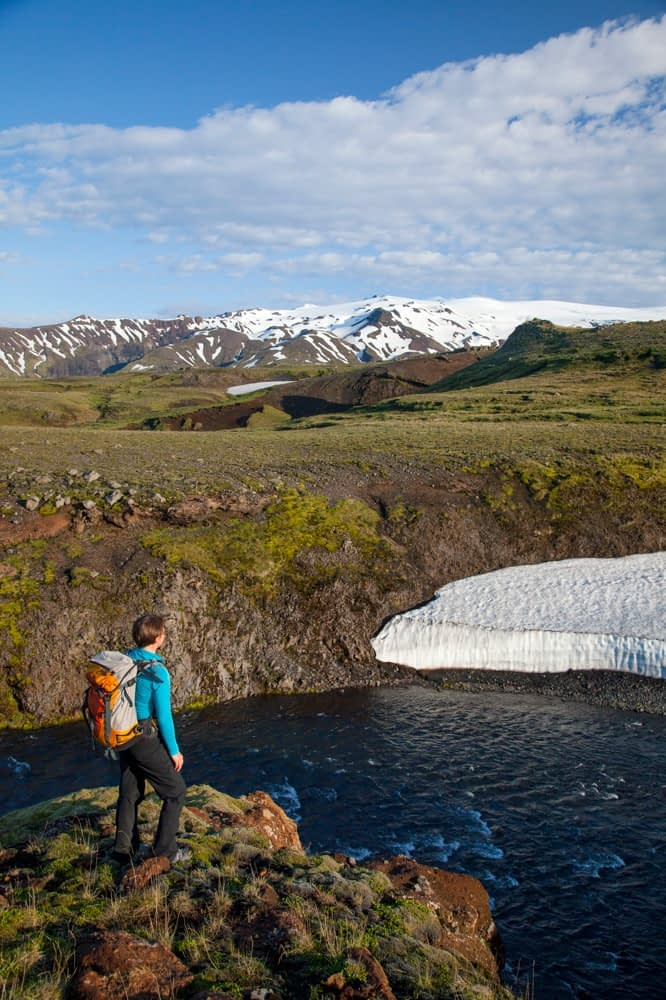 Hiker beside the Skogar river with Eyjafjallajokull above, Fimmvorduhals trail, Sudhurland, Iceland.