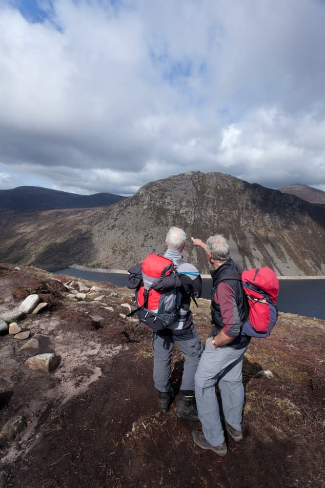 Two walkers looking out acros Ben Crom reservoir, Mourne Mountains, County Down, Northern Ireland.