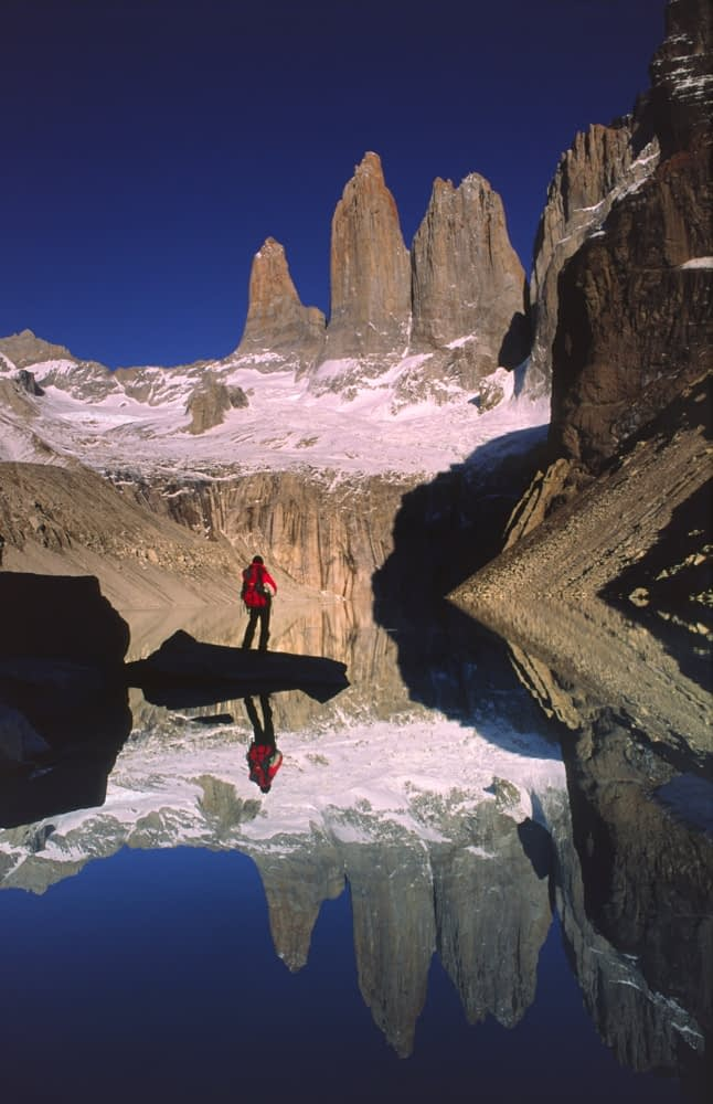 Reflection of trekker and the Torres del Paine, Torres del Paine NP, Patagonia, Chile.