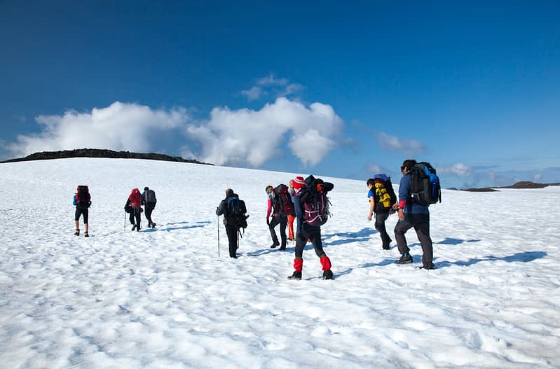 Hikers crossing snow on the Skogar to Fimmvorduhals trail, Sudhurland, Iceland.