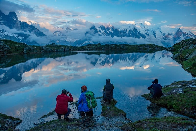 Photographers beside Lac des Cheserys, beneath the Mont Blanc massif, Chamonix Valley, French Alps, France.