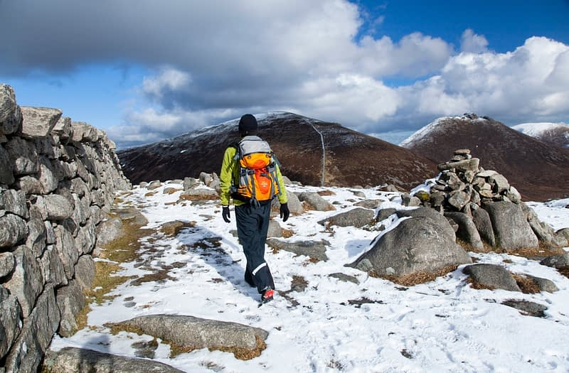 Winter walker on Slieve Loughshannagh, Mourne Mountains, Co Down, Northern Ireland.