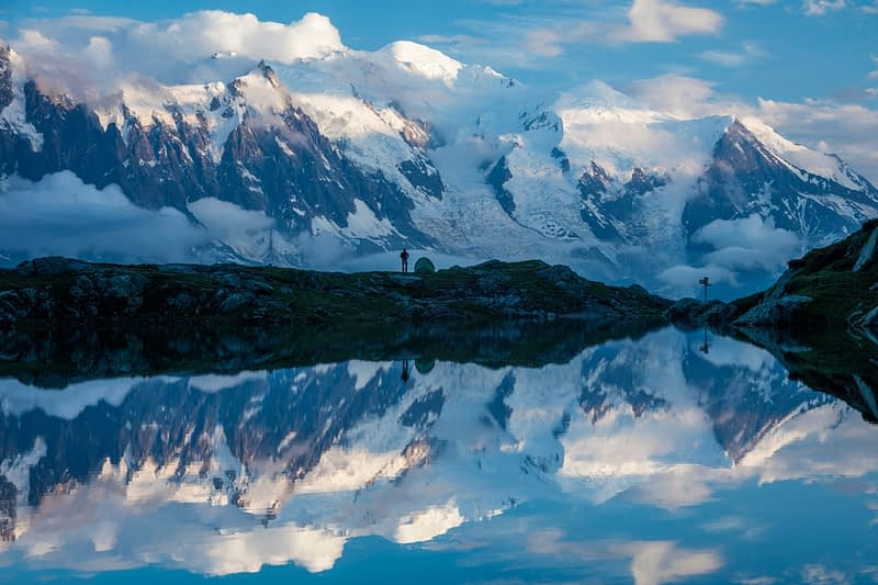 Hikers and Mont Blanc massif reflected in Lac des Cheserys, Chamonix Valley, French Alps, France.