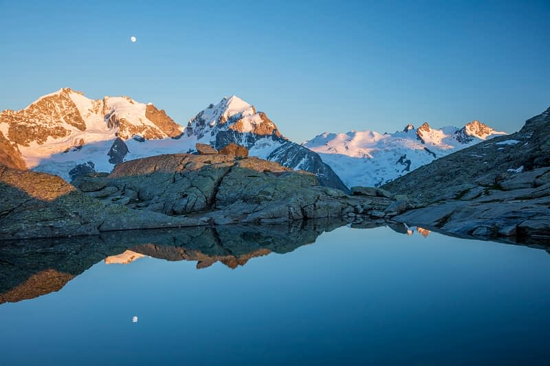 Reflection of moonrise over Piz Bernina and Piz Rosbeg, Fuorcla Surlej, Berniner Alps, Graubunden, Switzerland.