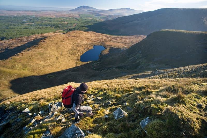 Walker climbing the slopes of Slieve Carr, Nephin Beg Mountains, Co Mayo, Ireland.