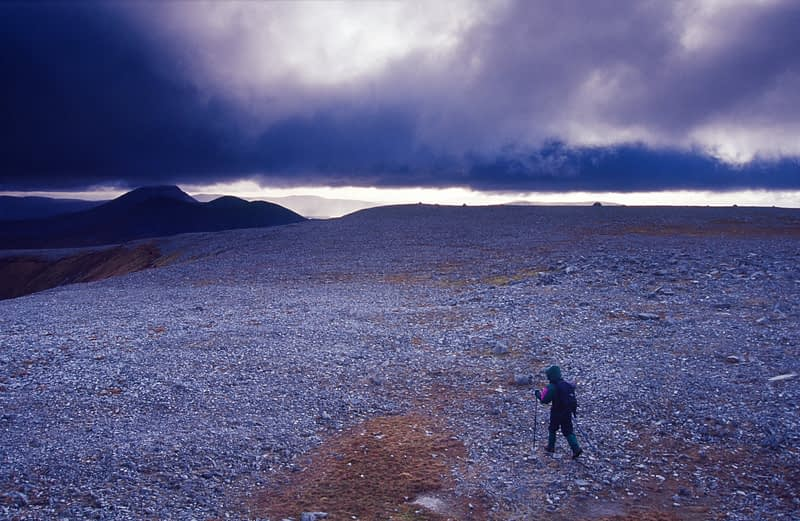 Walker heading southwest along the summit plateau of Muckish Mountain, County Donegal, Ireland.