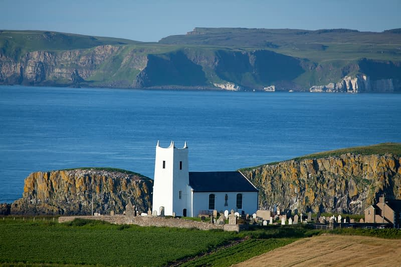 Ballintoy Church with Rathlin Island in the distance, County Antrim, Northern Ireland.