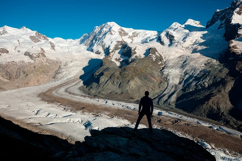Hiker silhouetted beside Gorner Glacier and Monte Rosa, Gornergrat, Zermatt, Switzerland.