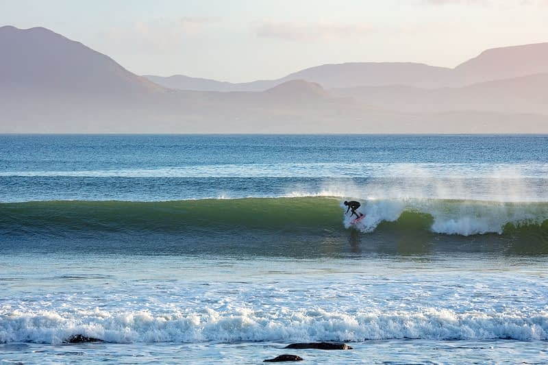 Surfer riding a wave at Mulranny, County Mayo, Ireland.