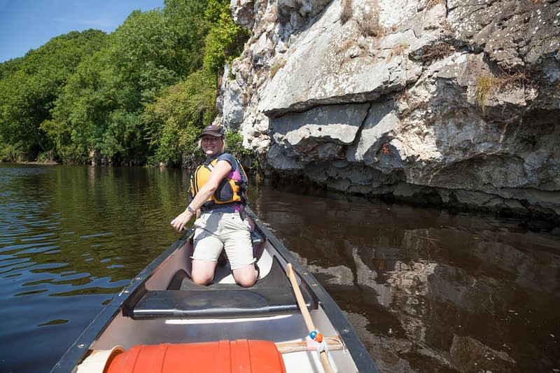 Canoeist beside a limestone outcrop, Blackwater River, Mallow, County Cork, Ireland.