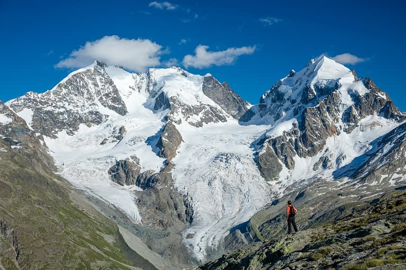 Hiker beneath Piz Bernina and Piz Rosbeg, Fuorcla Surlej, Berniner Alps, Graubunden, Switzerland.