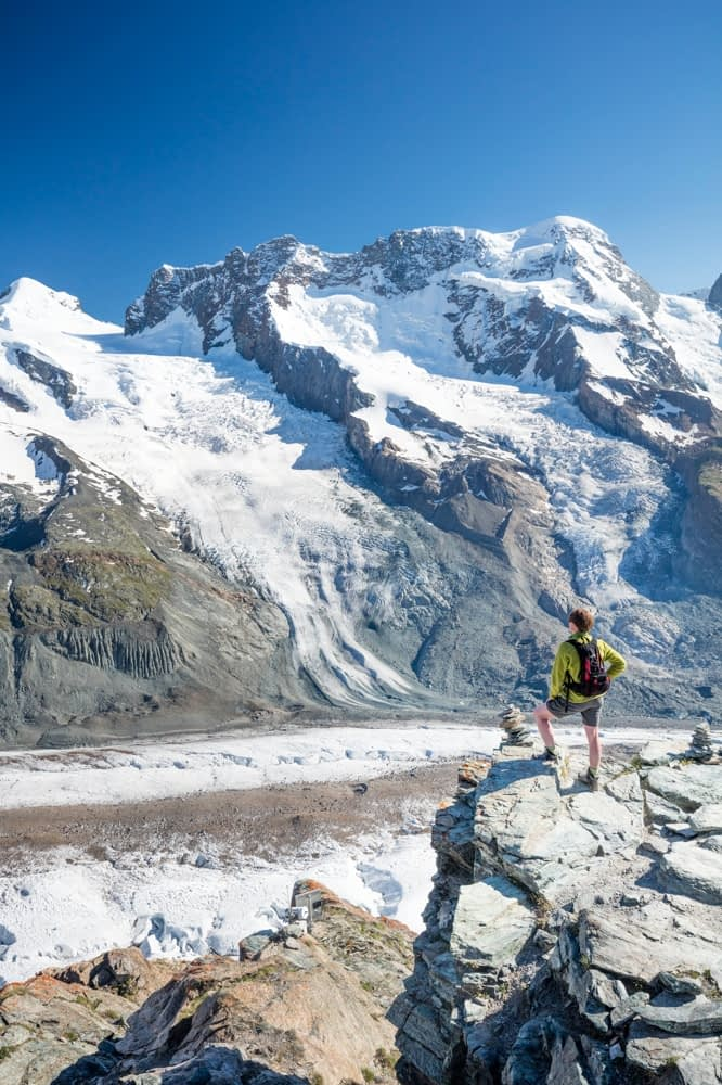 Hiker beside Gorner Glacier and Monte Rosa, Gornergrat, Zermatt, Switzerland.