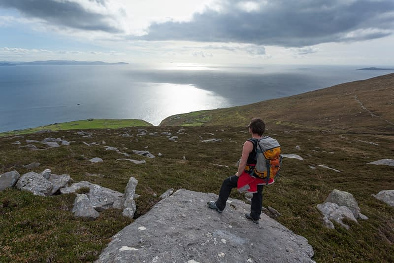 Walker looking across Dingle Bay from Eagle Mountain, Dingle Peninsula, County Kerry, Ireland.