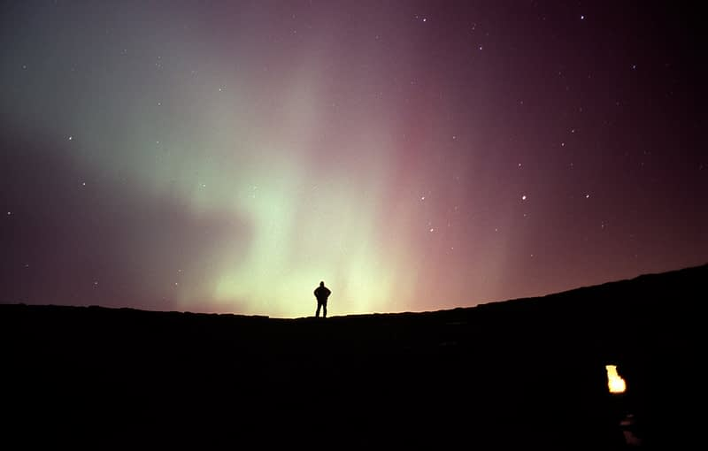 Northern lights and figure silhouetted, County Donegal, Ireland.