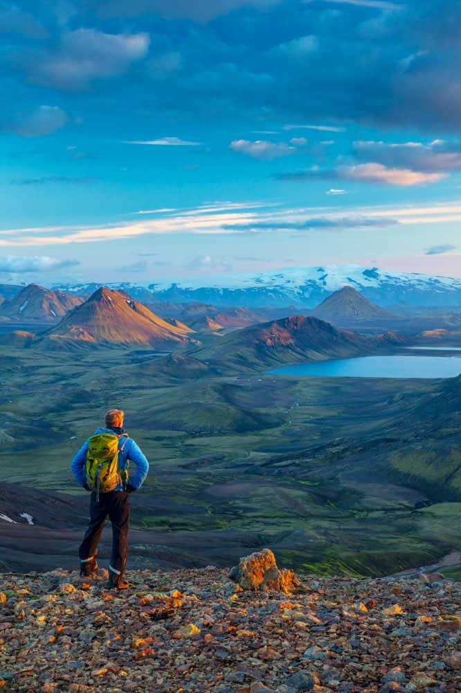 Evening hiker looking over the mountains and lake at Alftavatn, from Jokultungur on the Laugavegur hiking trail. Central Highlands, Sudhurland, Iceland.