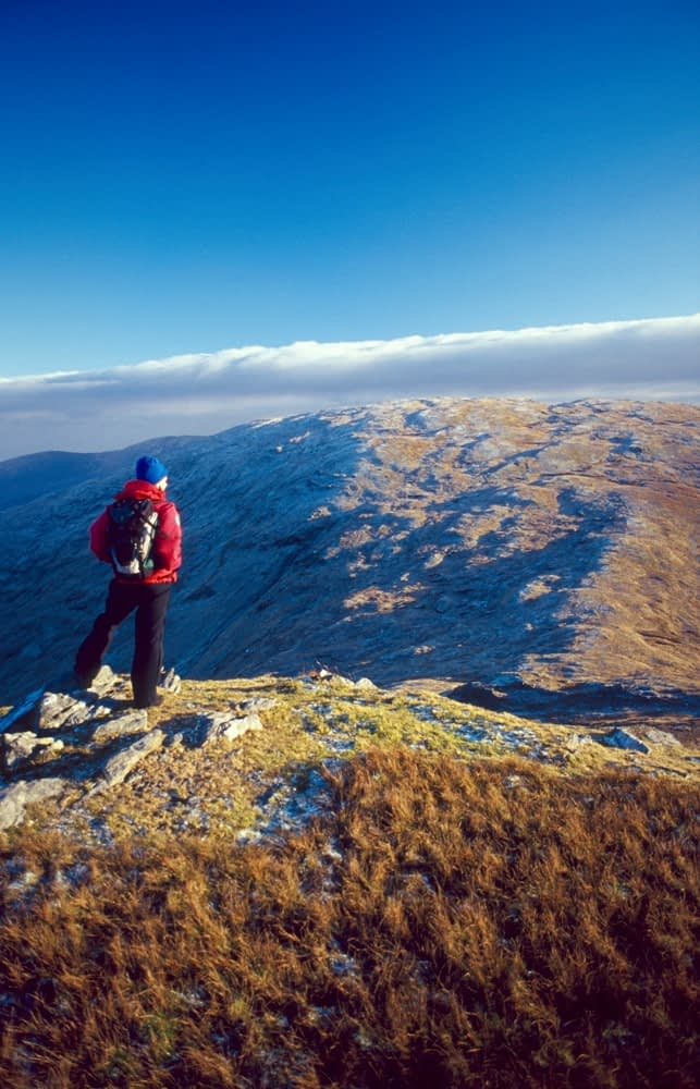 Winter walker near the summit of Lavagh Beg, Bluestack Mountains, County Donegal, Ireland.