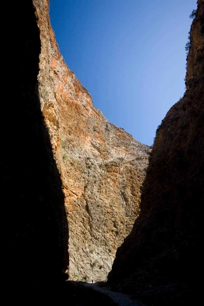 Hiker silhouetted at the base of the Aradena Gorge, White Mountains, Crete, Greece.