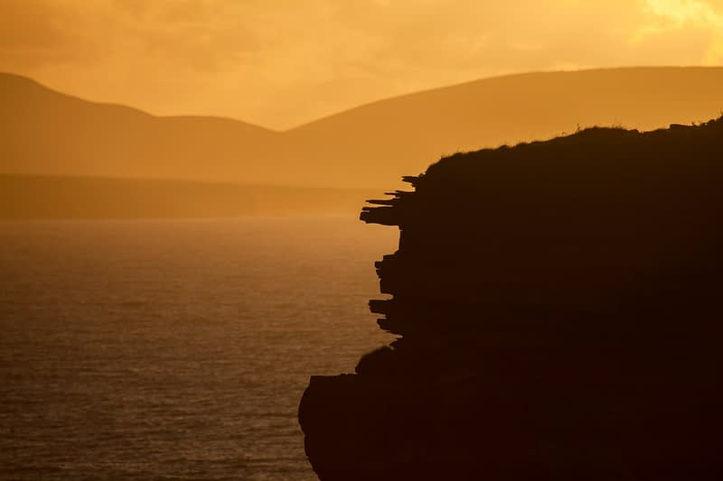 Downpatrick Head silhouetted at sunset, County Mayo, Ireland.