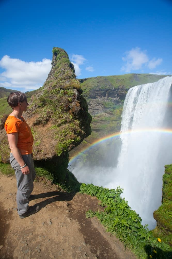 Person admiring 60m-high Skogafoss waterfall, Skogar, Sudhurland, Iceland.