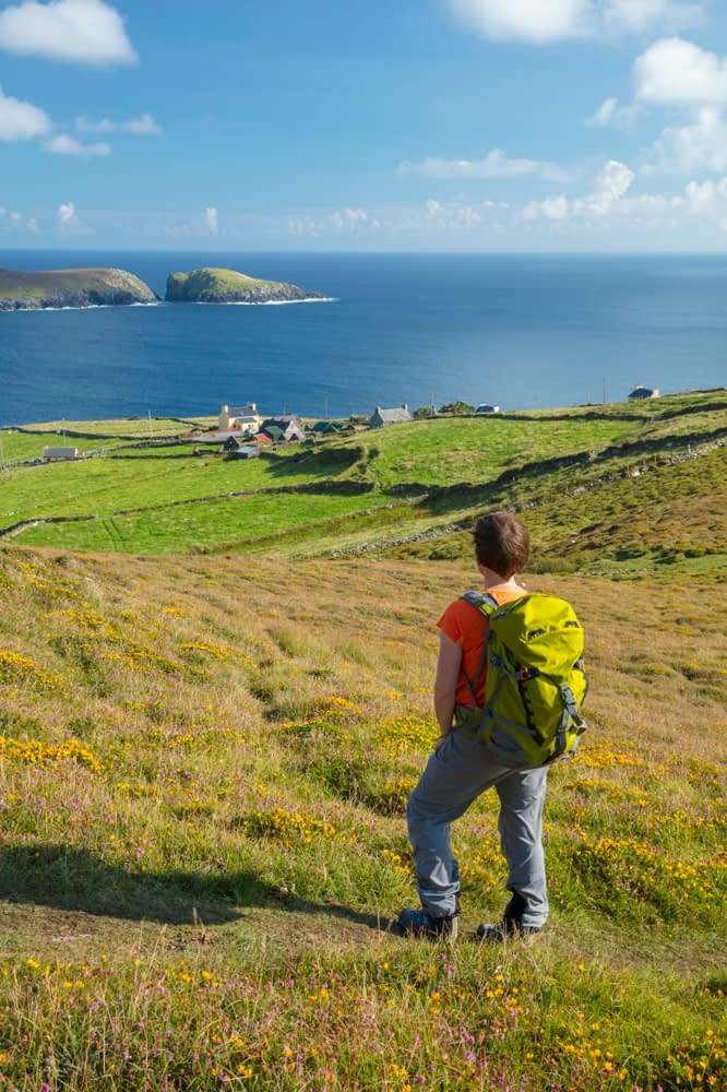 Hiker above the hamlet of Ballynacallagh, Dursey Island, Beara Peninsula, County Cork, Ireland.