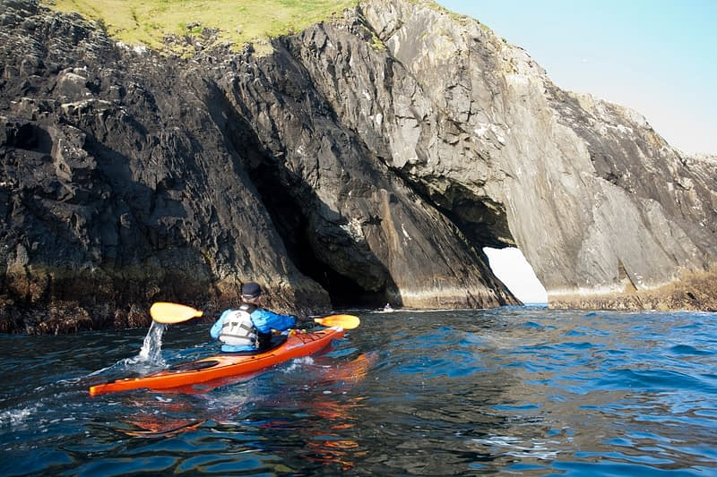 Sea kayaker beside a rock arch, Stags of Broadhaven, Portacloy, Co Mayo, Ireland.