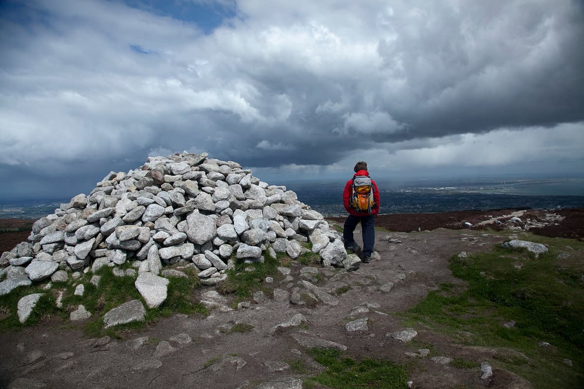 Walker beside the cairn and megalithic passage tomb at the summit of Fairy Castle (536m), Dublin Mountains, County Dublin, Ireland.