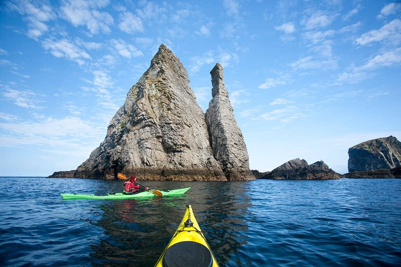 Sea kayaker exploring seastacks near Port, County Donegal, Ireland.