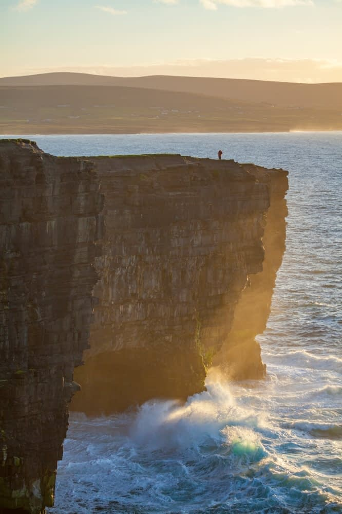 Evening figure at on the cliffs of Downpatrick Head, County Mayo, Ireland.