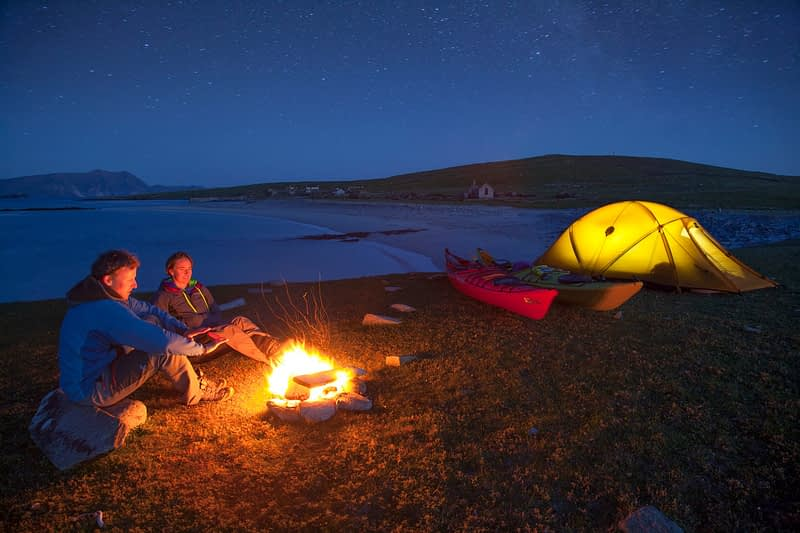 Sea kayakers enjoying an evening campfire, Inishkea South Island, County Mayo, Ireland.