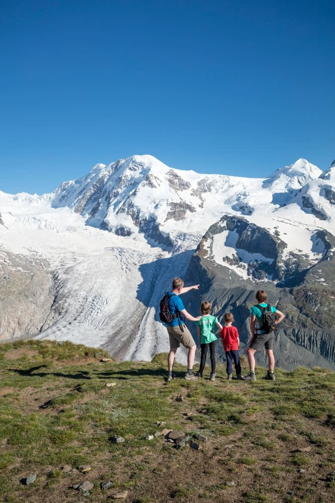 Hiking family beneath Monte Rosa, Gornergrat, Zermatt, Switzerland.