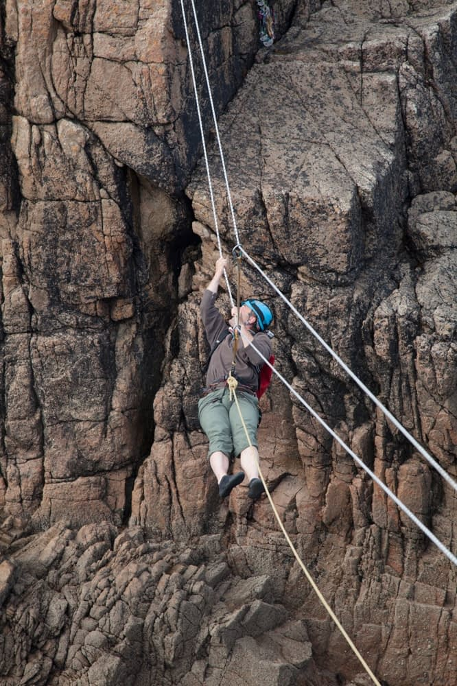 Rock climber crossing a tyrolean traverse, Gwedore, County Donegal, Ireland.