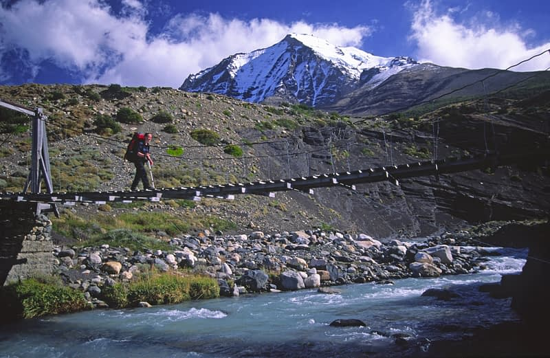 Trekker on bridge over the Rio Ascensio, Paine Circuit, Torres del Paine NP, Patagonia, Chile.