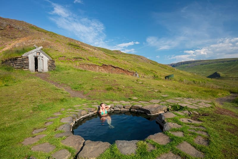 Woman bathing in Gudrunarlaug geothermal pool. Laugar, Saelingsdalur, west Iceland.