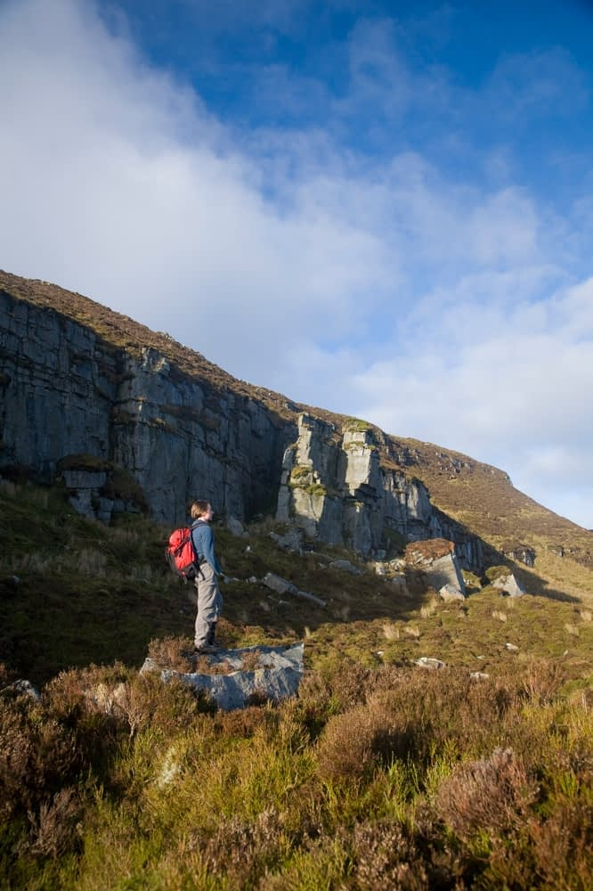 Walker beneath the Slieve Anierin escarpment, Co Leitrim, Ireland.