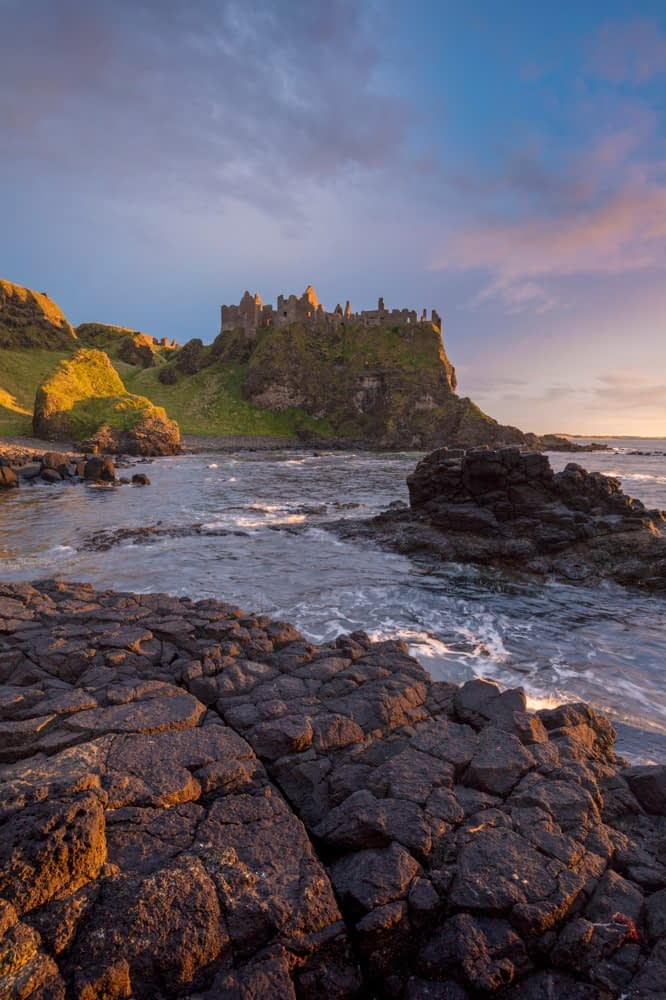 Coastal sunset beneath Dunluce Castle, County Antrim, Northern Ireland.