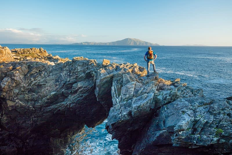 Hiker standing on a sea arch, Dooega Head, Achill Island, Co Mayo, Ireland.
