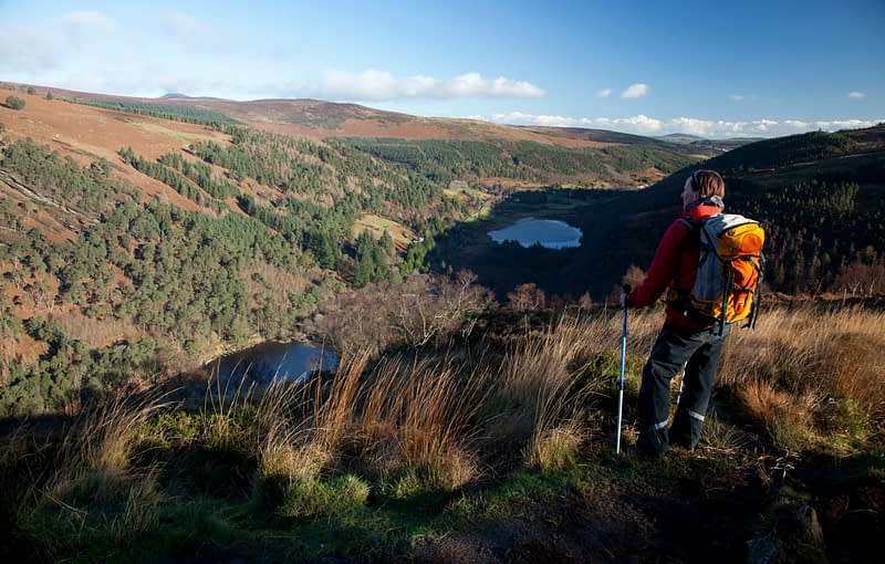 Walker looking over Glendalough from The Spinc, Wicklow Mountains National Park, County Wicklow, Ireland.