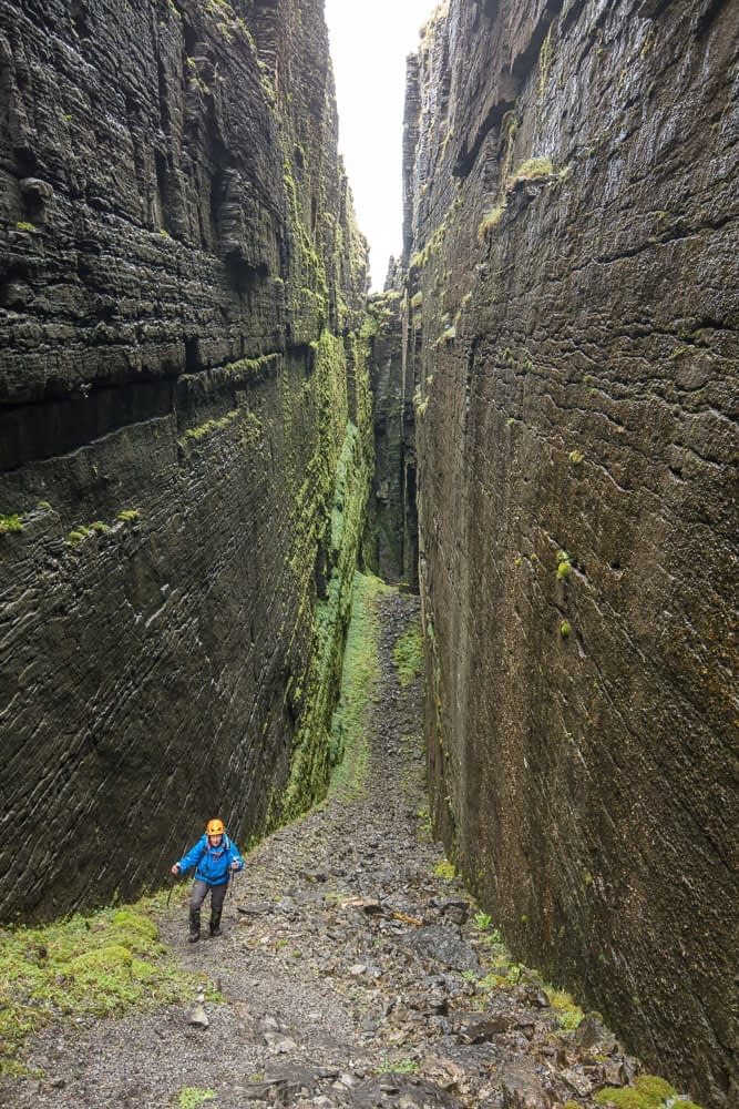 Hiker inside Annach Re Mhor chasm, Kings Mountain, County Sligo, Ireland.